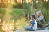 Grandfather and grandson fishing on pier