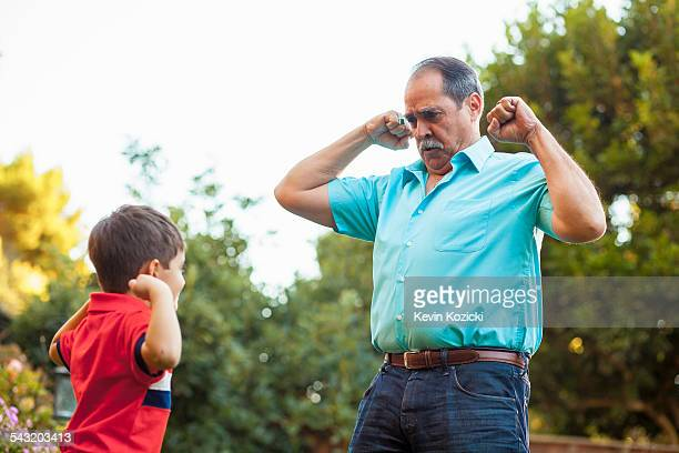 Grandfather and grandson flexing arms in garden