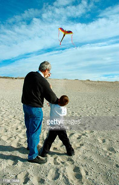Grandfather and grandson flying a kite on the beach