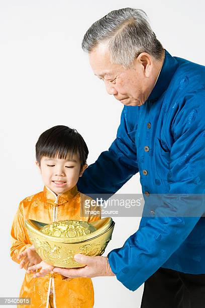 Grandfather and grandson holding a yuanbao