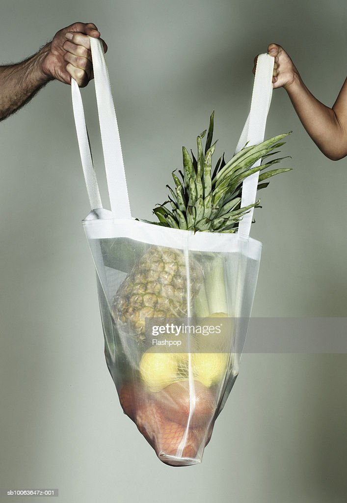 Grandfather and grandson (4-5) holding bag full of fruits, close-up : Stock Photo