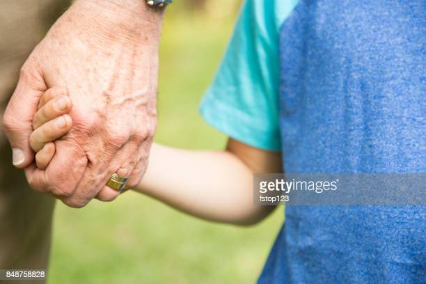 Grandfather and grandson holding hands outdoors together.