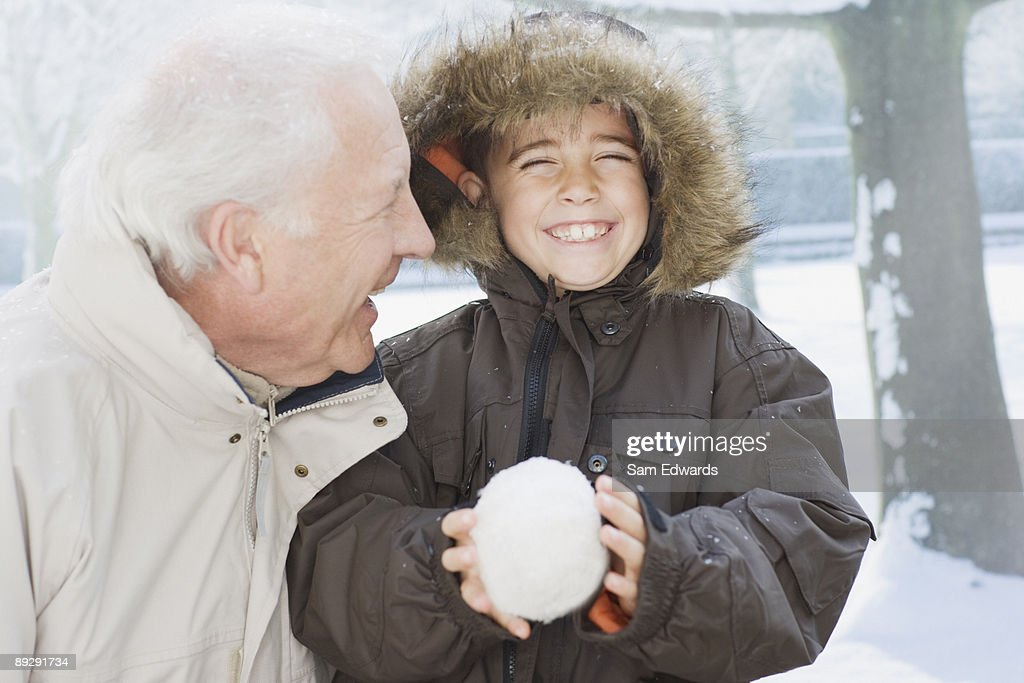 Grandfather and grandson holding snowball : Stock Photo