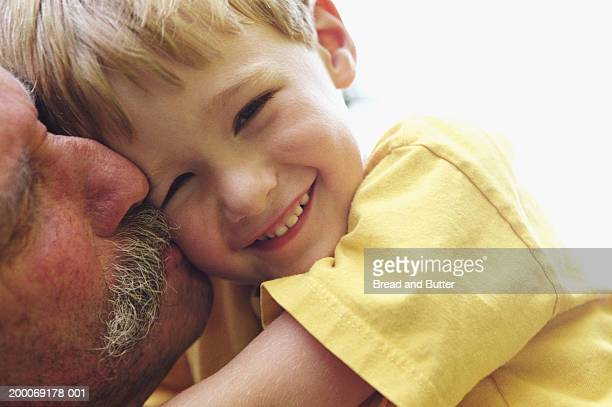 Grandfather and grandson hugging, close-up