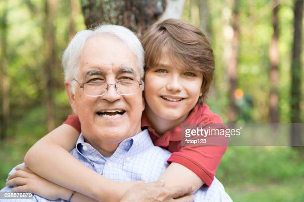 Grandfather and grandson hugging outdoors together.