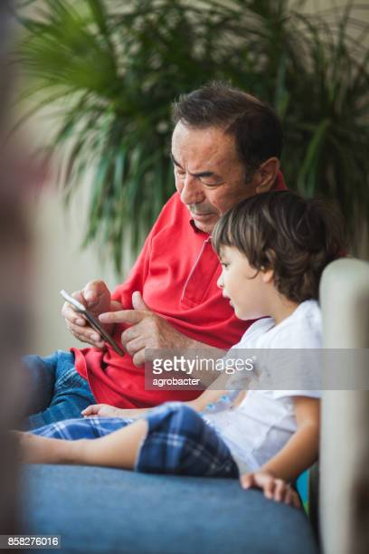 Grandfather and grandson looking a smartphone
