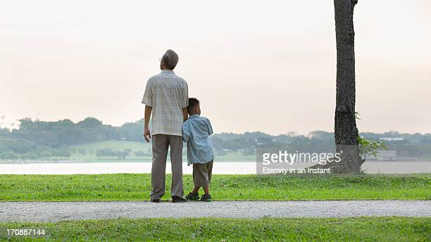Grandfather and grandson looking at lake
