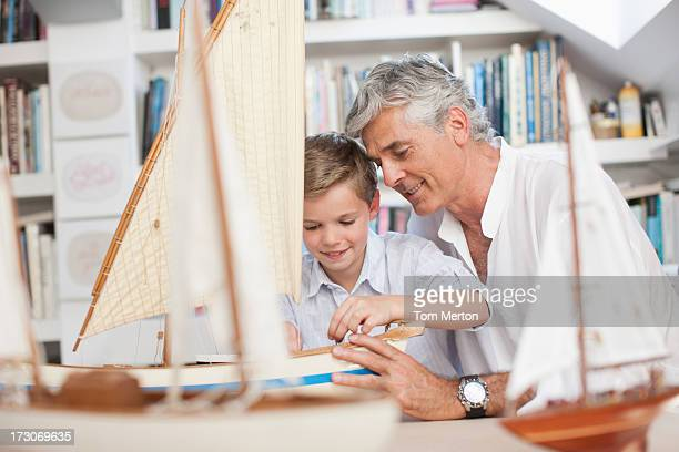 Grandfather and grandson looking at model sailboats