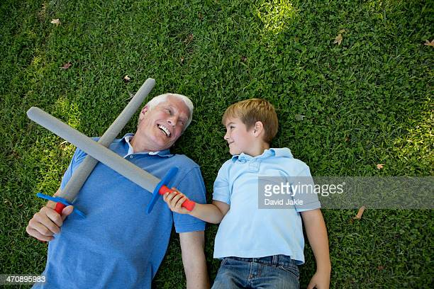 Grandfather and grandson lying on grass with toy swords