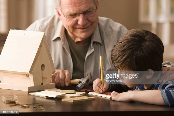 Grandfather and grandson making birdhouse