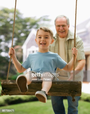 Grandfather and grandson on swing : Stock Photo