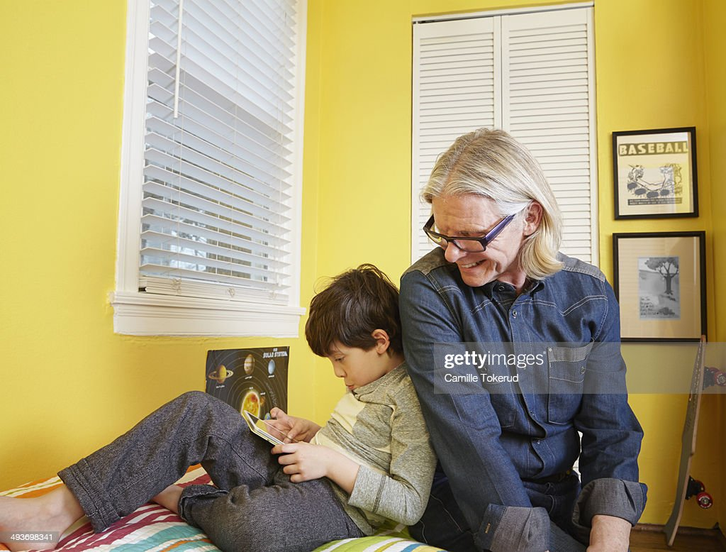 Grandfather and grandson on the bed playing : Stock Photo