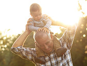 Grandfather carrying grandson on shoulders in park on sunny autumn day