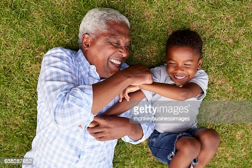 Grandfather and grandson play lying on grass, aerial view : Stock Photo