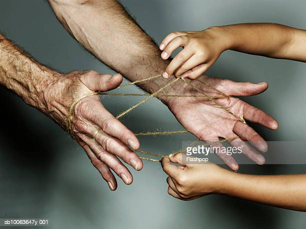 Grandfather and grandson (6-7) playing cat's cradle, close-up