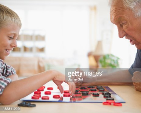 Grandfather and grandson playing checkers