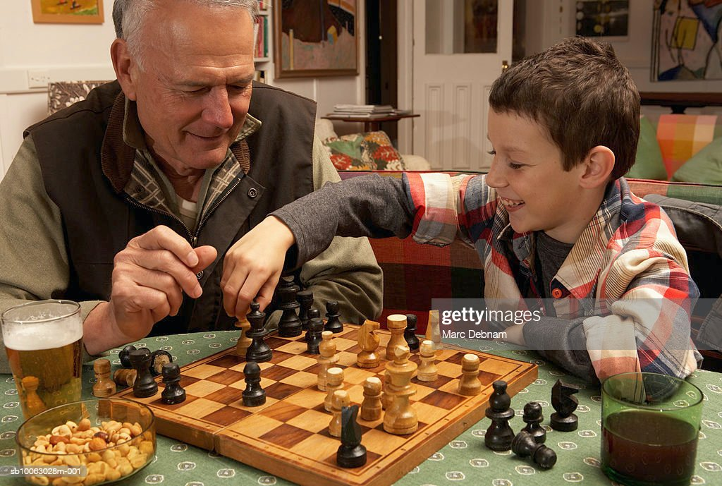 Grandfather and grandson (10-11) playing chess at home : Stock Photo