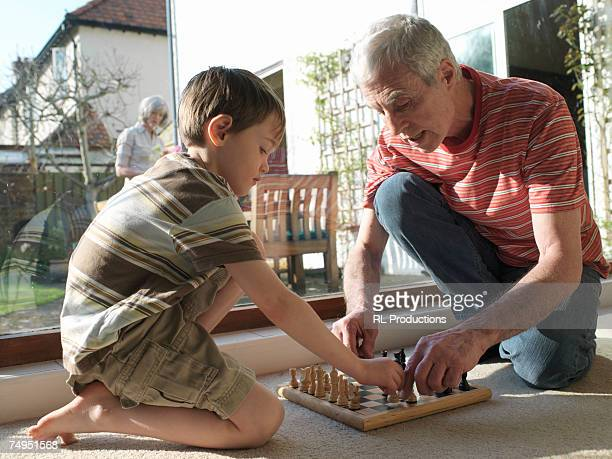 Grandfather and grandson (5-7) playing chess on floor