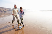 Grandfather And Grandson Playing Football On Winter Beach Together