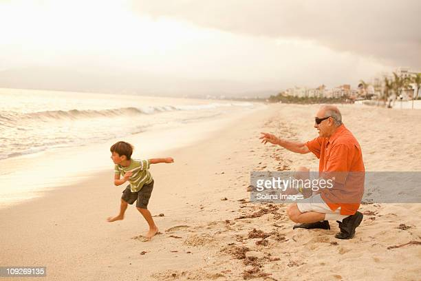 Grandfather and grandson playing on beach together