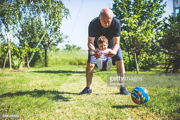 Grandfather and grandson playing with ball