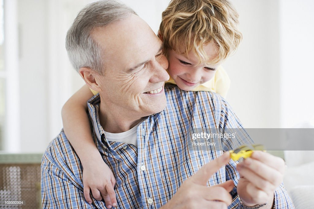 Grandfather and grandson playing with toy car : Stock Photo
