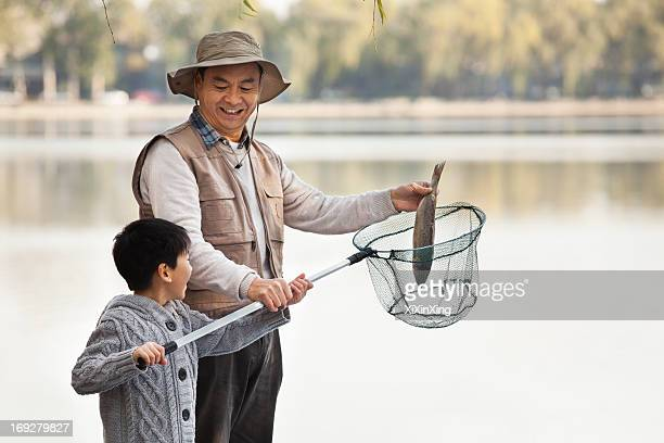 Grandfather and grandson putting fish into net at lake
