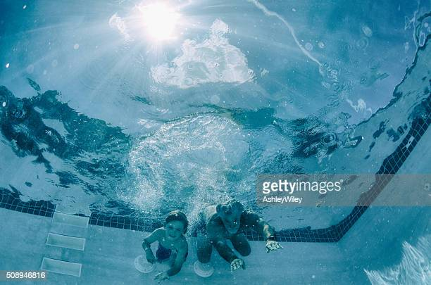 Grandfather and Grandson race underwater in a pool in summer