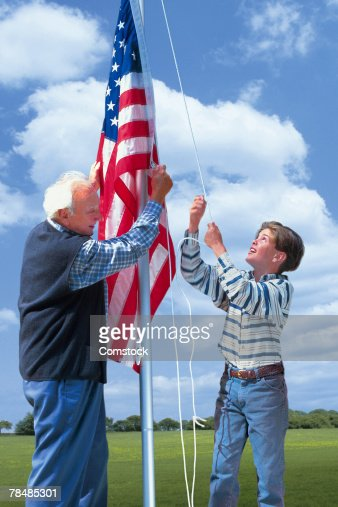 Grandfather and grandson raising the American flag