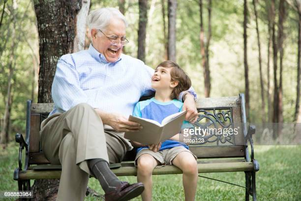 Grandfather and grandson reading books outdoors together.