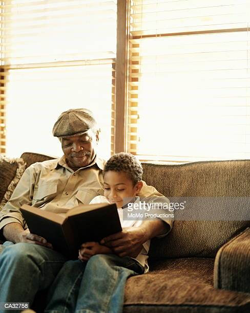 Grandfather and grandson (5-7) reading on sofa
