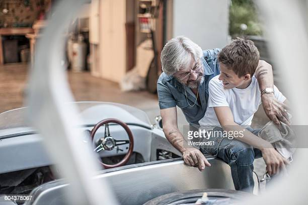 Grandfather and grandson restoring a car together