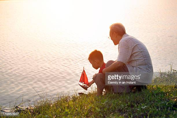 Grandfather and grandson sailing model boat
