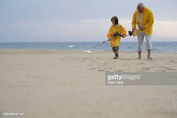 Grandfather and grandson (5-7) searching on beach with metal detector