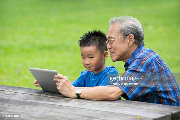 Grandfather and grandson sharing tablet device
