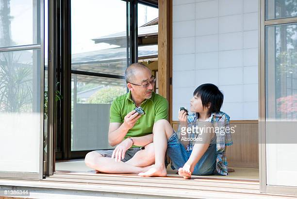 Grandfather and grandson (8-9) sitting and eating rice ball in porch