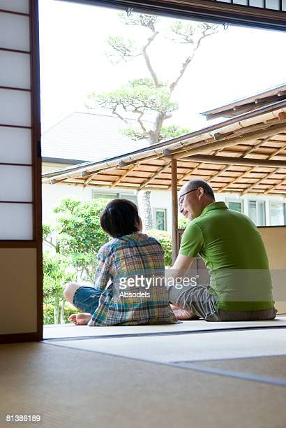 Grandfather and grandson (8-9) sitting and talking in porch, vertical, rear view