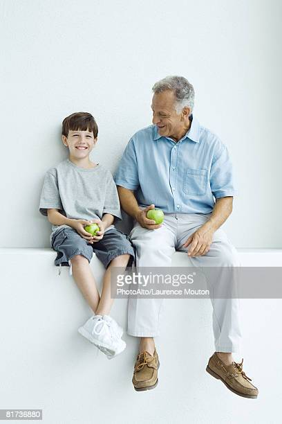 Grandfather and grandson sitting side by side on ledge, holding apples, both smiling