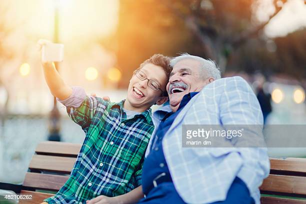 Grandfather and grandson taking a selfie in the park