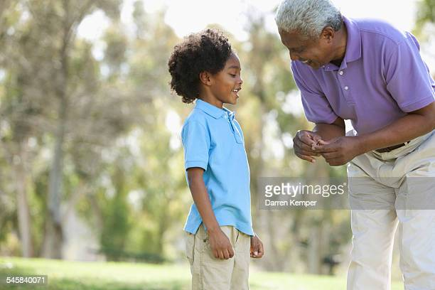 Grandfather and grandson (7-9) talking in park