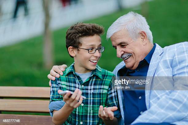 Grandfather and grandson talking in the park