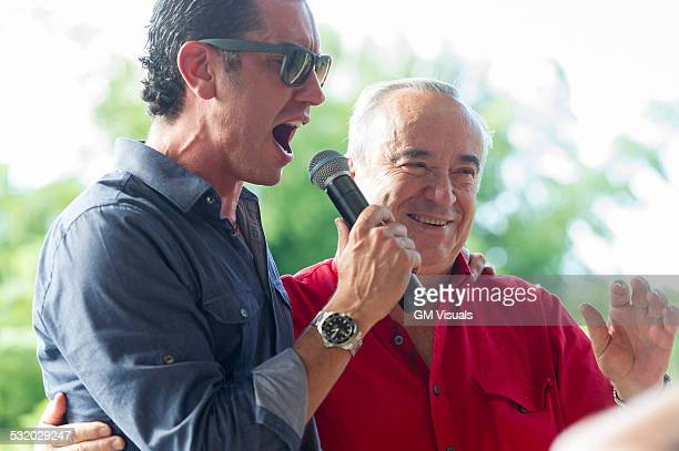 Grandfather and grandson talking into microphone at family reunion