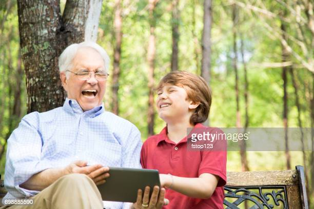 Grandfather and grandson using digital tablet outdoors together.