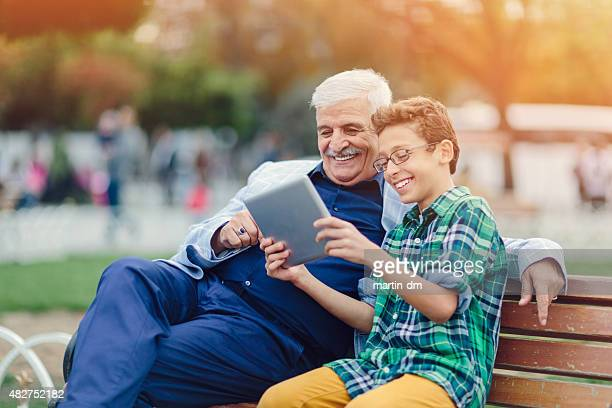 Grandfather and grandson using tablet in the park