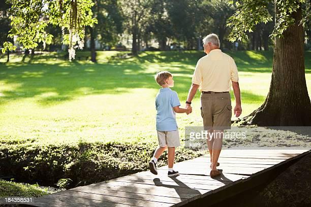 Grand-père et son petit-fils à pied dans le parc