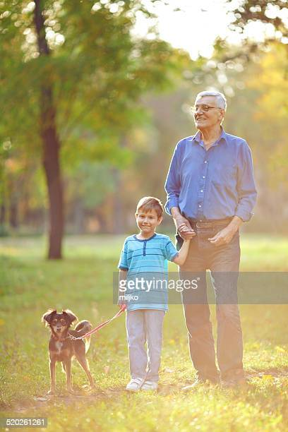 Grandfather and grandson walking in park