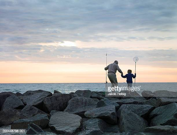 Grandfather and grandson (4-6) walking on rocks with fishing equipment