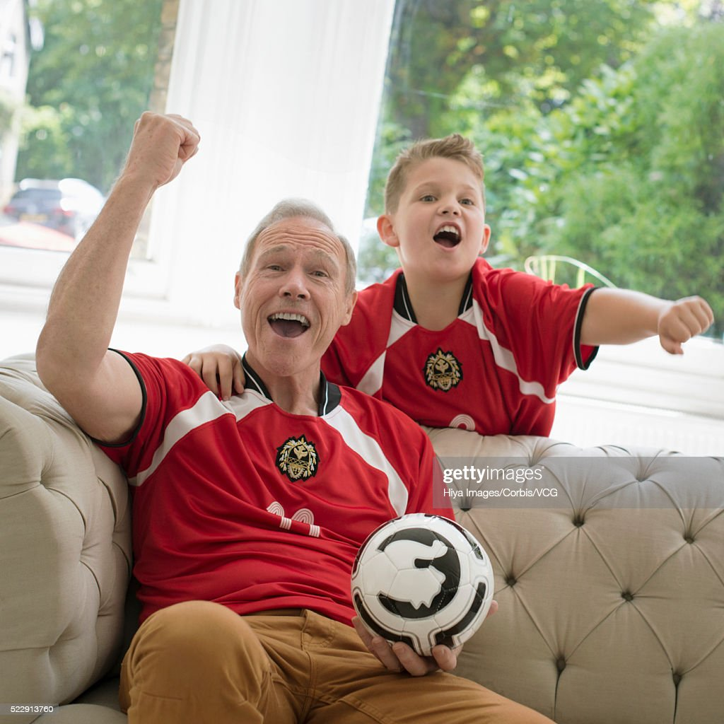 Grandfather and grandson (10-12 years) watching sports event