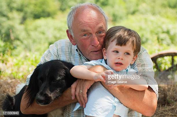 Grandfather and grandson with dog, portrait