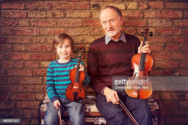 Grandfather and grandson with violins